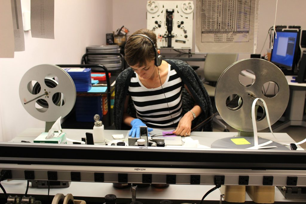 Archives assistant Amy San Pedro cleaning film before it's digitize.