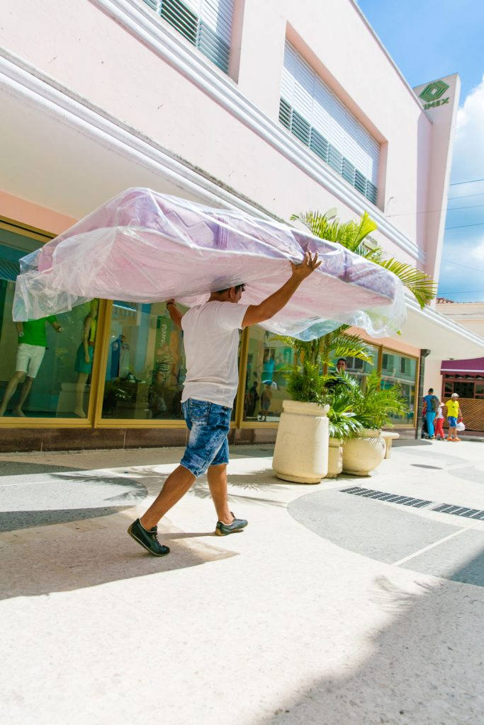 A man carrying a newly bought mattress to his home.