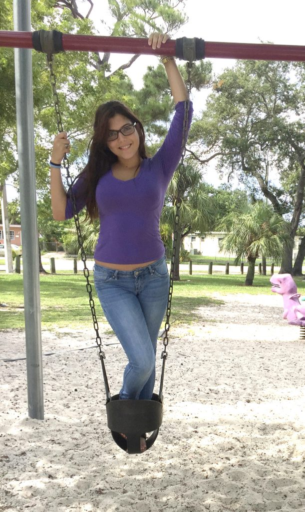 Jael Valencia on a swing in the park.