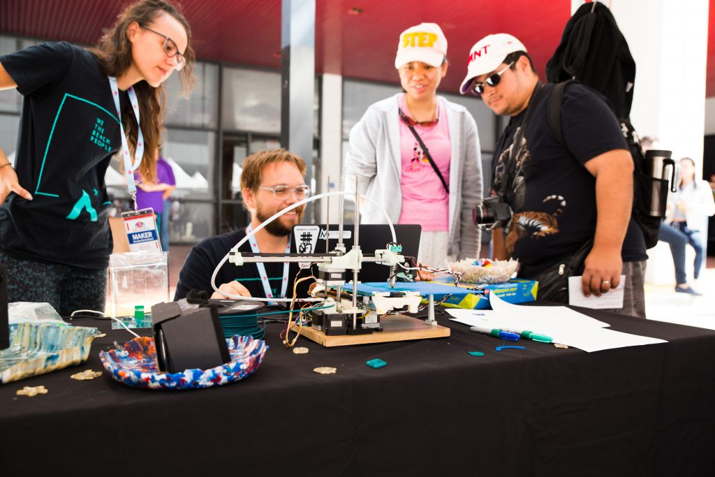 A group looking over a 3D printer.