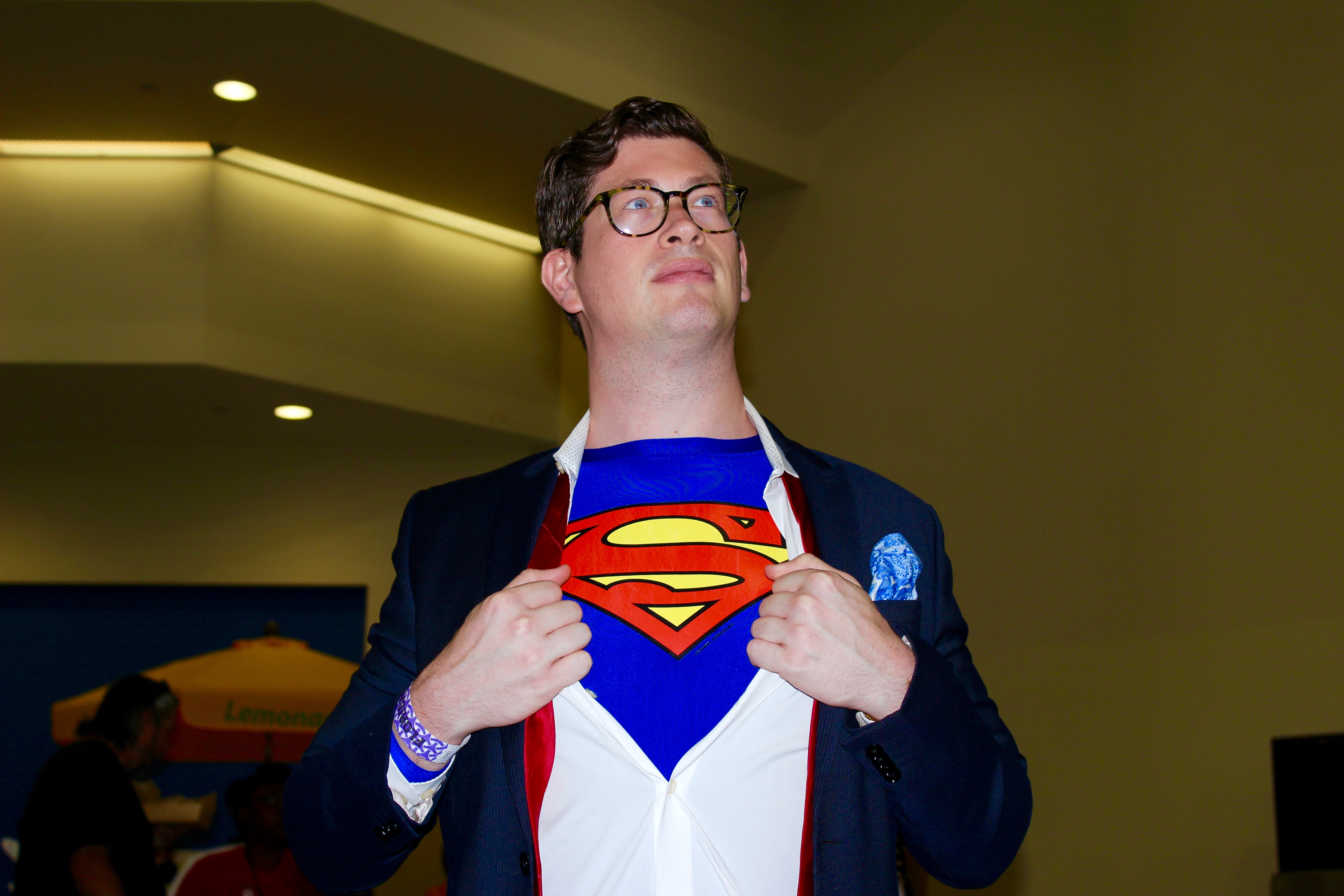 A cosplayer dressed as Clark Kent/Superman.