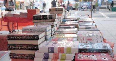 Piles of books on a table.