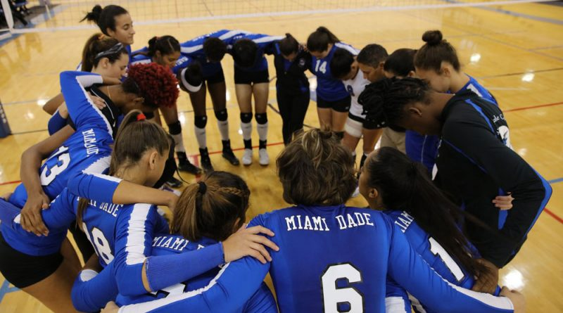 The Lady Sharks volleyball team huddled together.