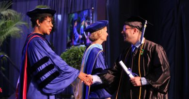 Student receiving his degree on stage.