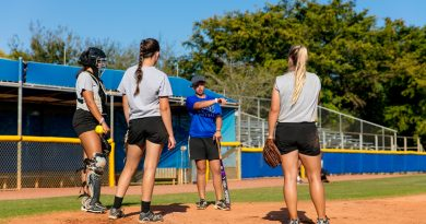 Lady Sharks softball team players on the field practicing.