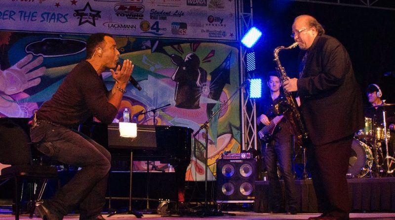 Jon Secada and Ed Calle performing on stage.