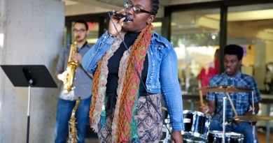 Jenna Gunter of Vocal Fusion performing along with the band in front of Koffehouse in Kendall Campus.