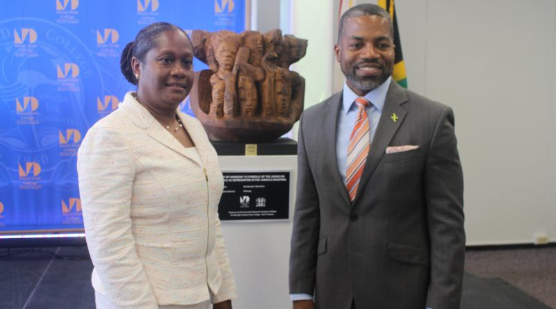 North Campus President Malou C. Harrison and Consulate General of Jamaica Franz Hall posing in front of the sculpture.