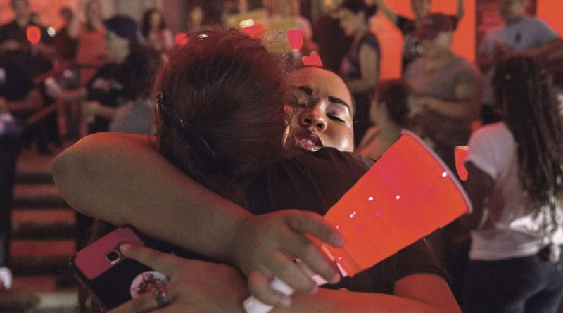 Sisters hugging in front of the Freedom Tower during a DACA vigil.