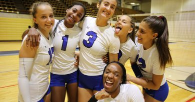 The volleyball team posing for the camera.