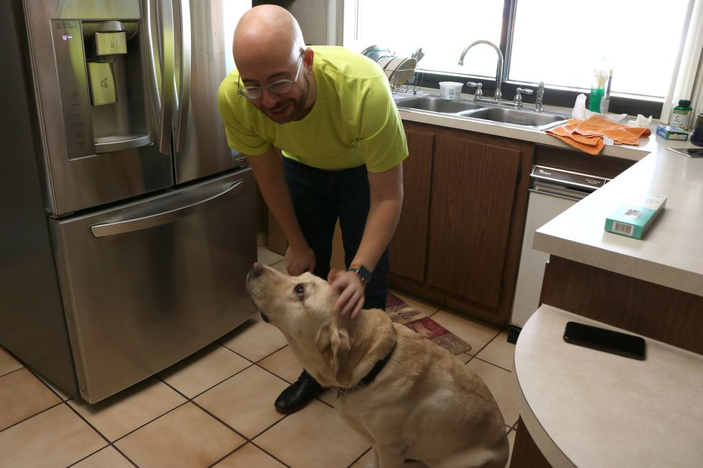 Gabriel with his guide dog Posh in the kitchen.