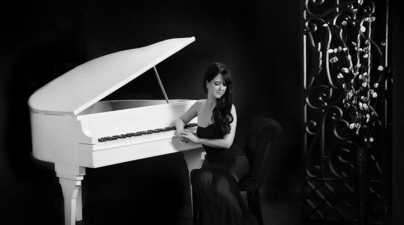 Ana Rodriguez with her piano in a glamour shot.