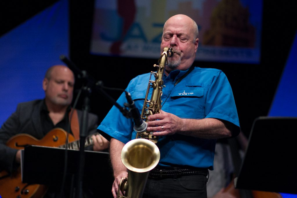 Saxophonist Mark Colby performing on stage.