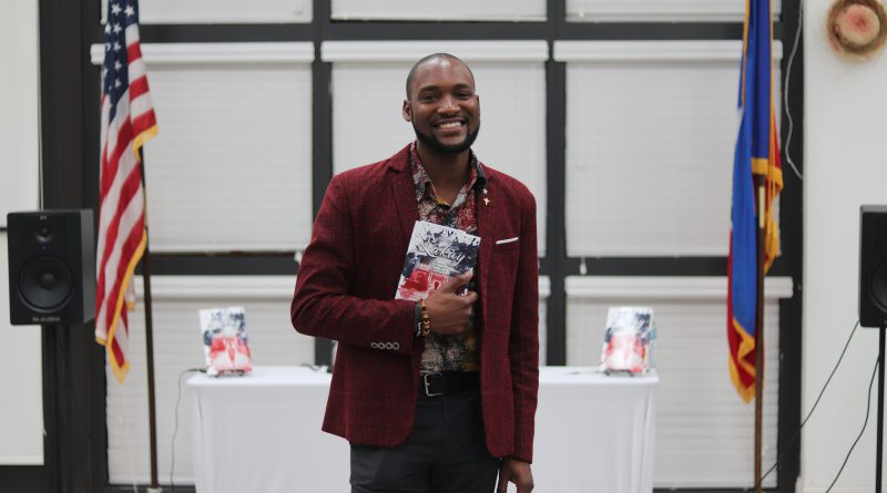 Haitian author David Frederick posing for the camera with his book.