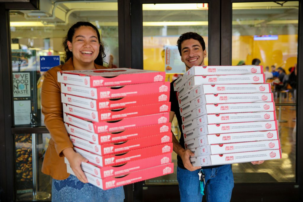 Students carrying boxes of pizza.