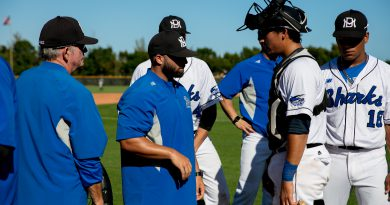 Assistant coach talking to catcher.