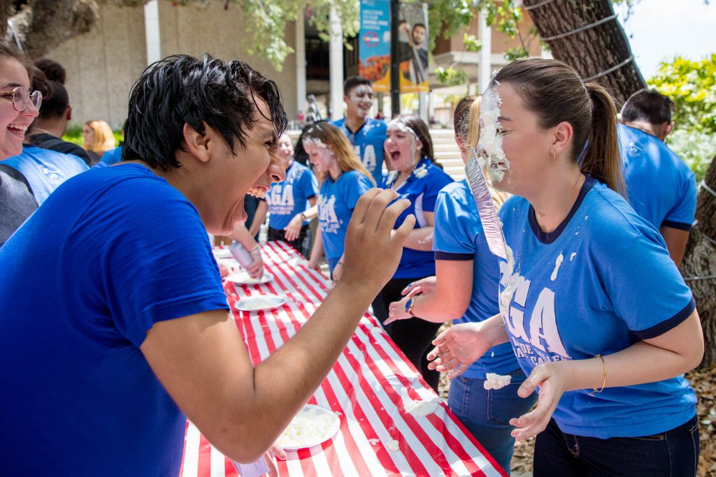 Students laughing at one with pie on her face.