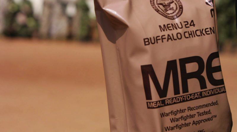 A soldier holding a bag of MRE.