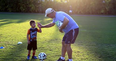 "Antonio ""Motor"" Paz high fives a child."