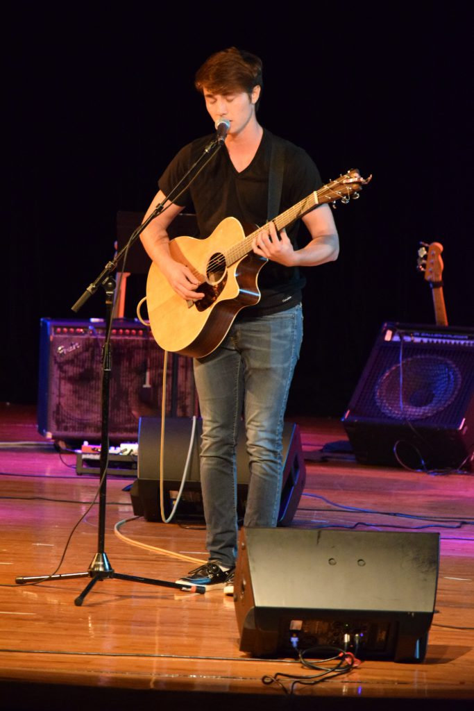 Student playing his guitar on stage.