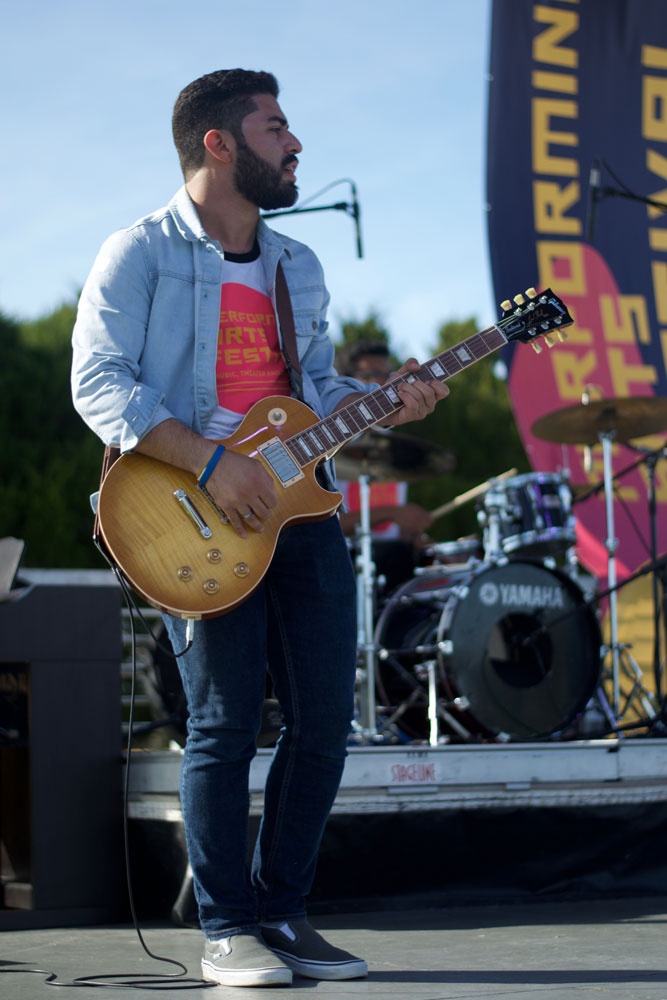 Student Jonathan Diaz playing guitar on stage.