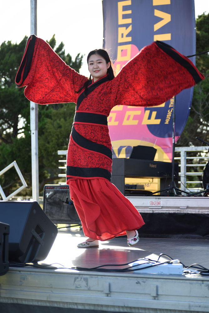 Jue Chou performing a Chinese folk dance on stage.