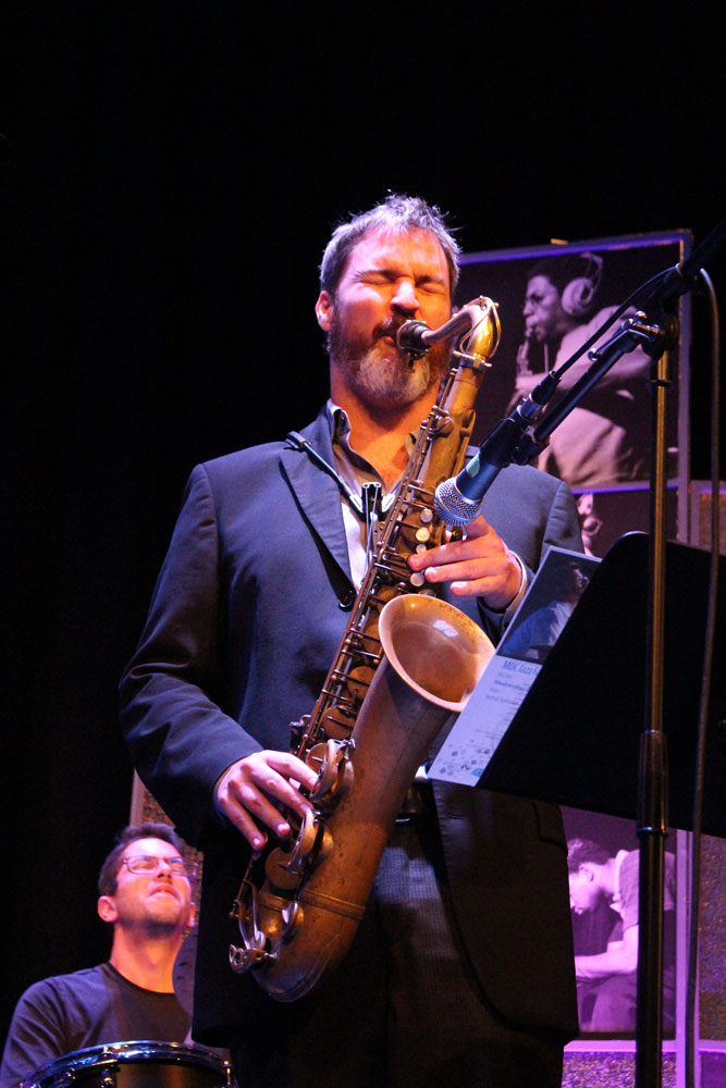 Mark Small playing the saxophone on stage.