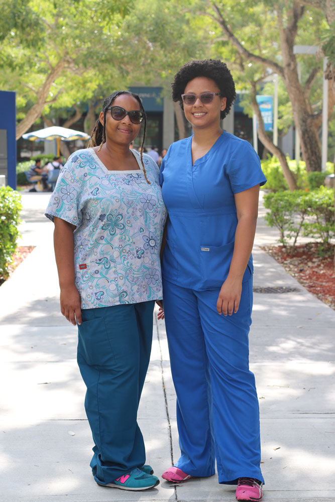 Mother and daughter posing for the camera wearing their nurse scrubs.