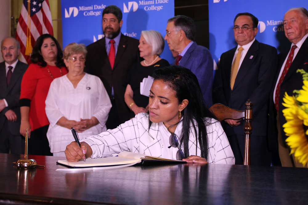 A woman signing the Agreement for Democracy in Cuba.