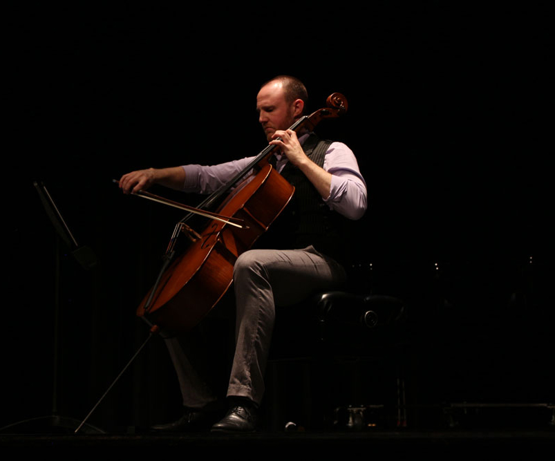 Bryan Hayslett playing the cello on stage.