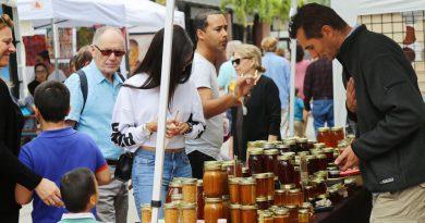 People gathering around jars of honey.