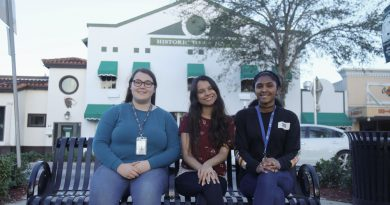 Students Franchesca Carr, Lydia Hussain and Samarah Martin sitting in front of the Historic Homestead Town Hall Museum.