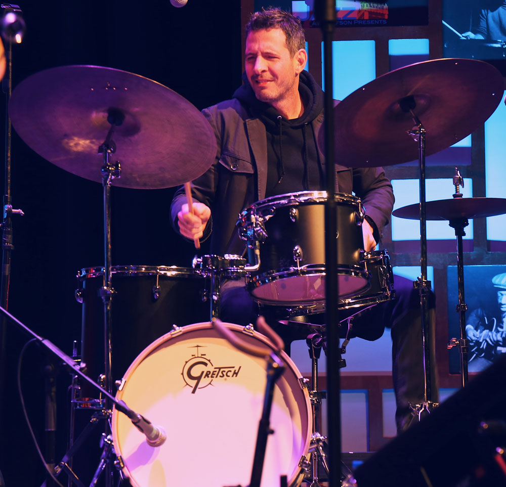 Jason Tiemann playing the drums on stage.