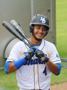 Shortstop Raphy holding two bats.