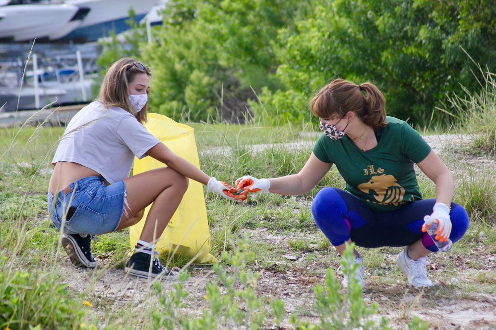 Two young women cleaning up trash.